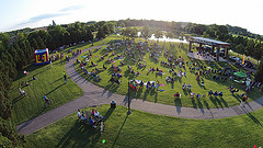 A drone view of Heritage Park showing green park with people watching a concert